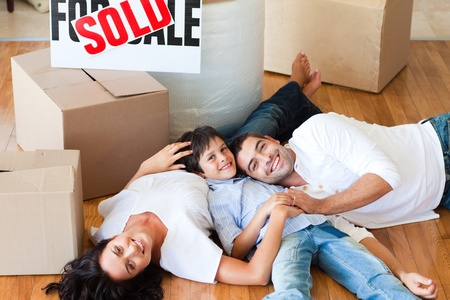 Parents and son moving house lying on floor photo