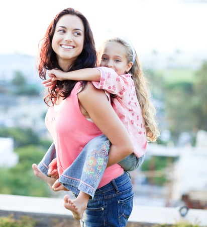 piggyback ride: Mother giving daughter piggyback ride