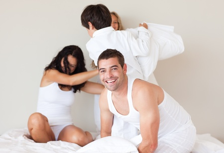 Delighted family having fun in a bedroom photo