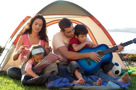 Happy family playing a guitar in a tent photo