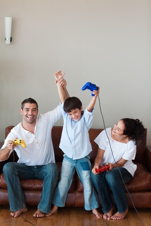 Delighted family playing video games in the living-room Stock Photo - 10076324