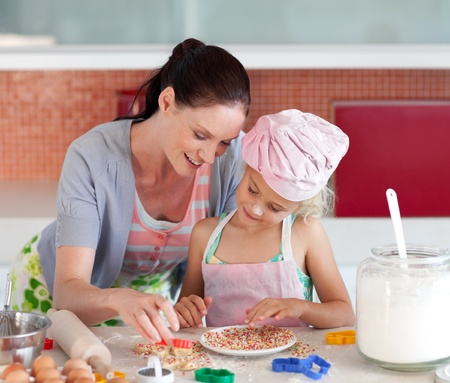 Delighted mother and her daughter baking in a kitchen photo