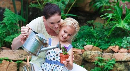 Radiant mother and daughter planting in their garden photo