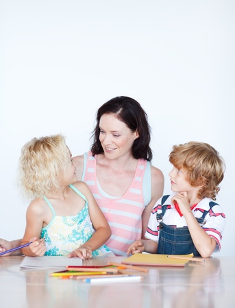 Mother helping her children doing homework photo