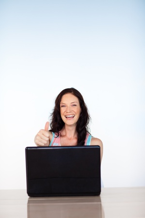Woman using her laptop with thumbs up and copy-space photo