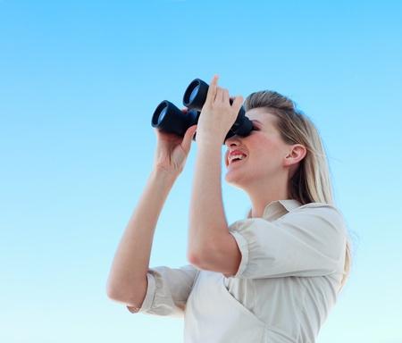 Blonde businesswoman looking through binoculars photo