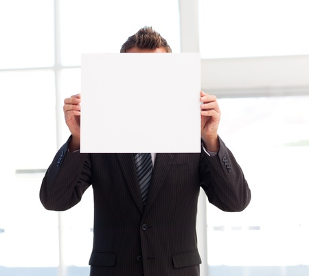 Businessman holding a white card in front of his face photo