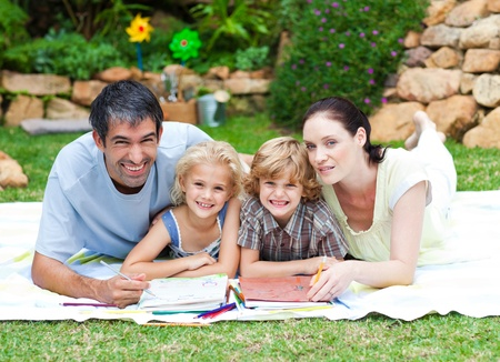 Happy family painting in a park smiling at the camera Stock Photo - 10070469
