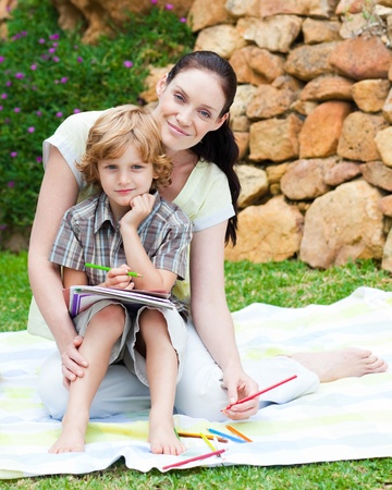 Mother and son drawing in a park photo