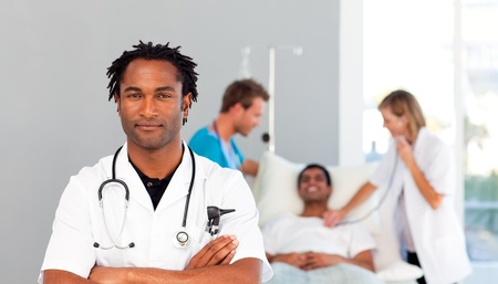 Serious doctor with folded arms and patient in the background photo