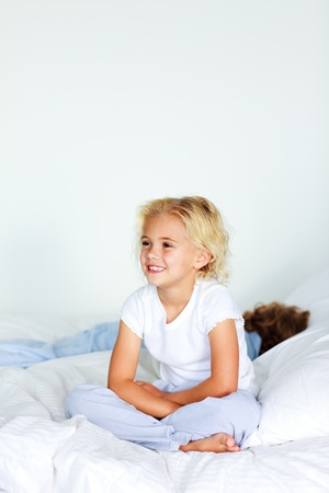 Little girl sitting in bed with copyspace photo
