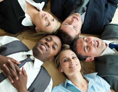 Closse-up of business people lying in a circle on the floor photo