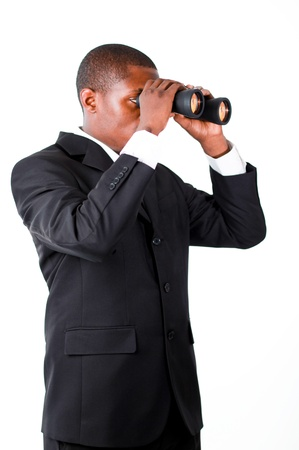 Young businessman looking with binoculars downwards photo