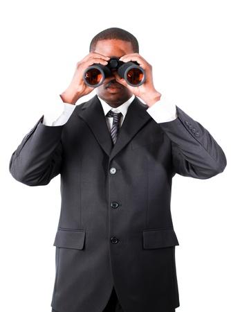 Serious businessman looking through binoculars photo