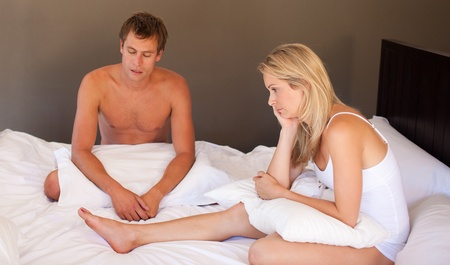 argues: Couple sitting on bed in silence