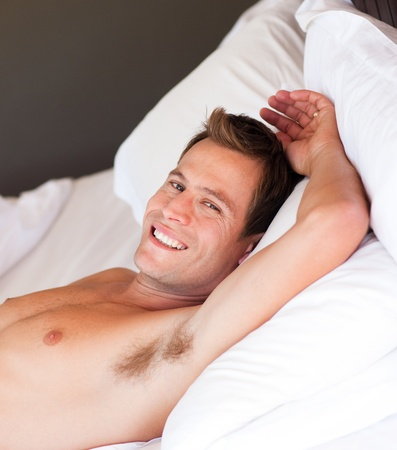 Smiling young man relaxing in bed photo