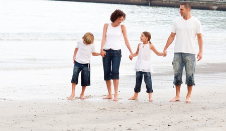 Family walking on a beach photo