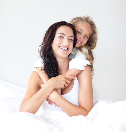 Beautiful mother and her daughter looking at the camera on the bed photo