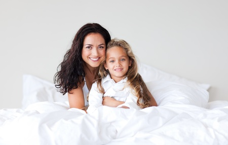 Confident mother and her daughter looking at the camera on the bed photo