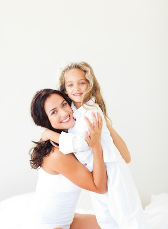 Cute mother and her daughter looking at the camera on the bed photo