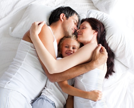 Parents and daughter relaxing on bed photo