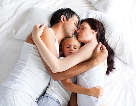 Happy little girl on bed with her parents Stock Photo - 10096496