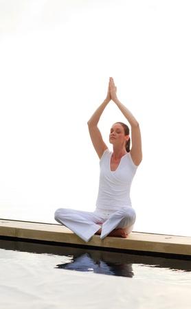 Woman doing yoga on the pool photo
