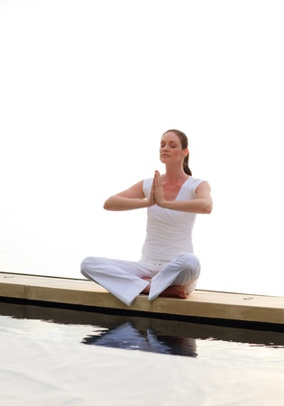 Woman doing yoga near the sea photo
