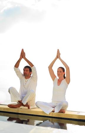 hombres haciendo ejercicio: Hombre y mujer haciendo yoga cerca del mar Foto de archivo