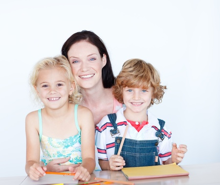 learning by doing: Children doing homework with their mother smiling at the camera
