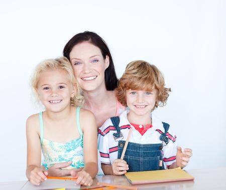 deberes: Ni�os haciendo deberes con su madre sonriendo a la c�mara