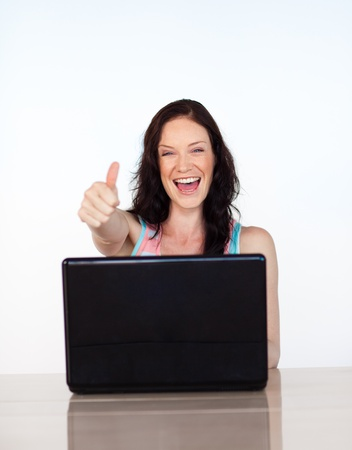 Happy woman with thumbs up using her laptop photo