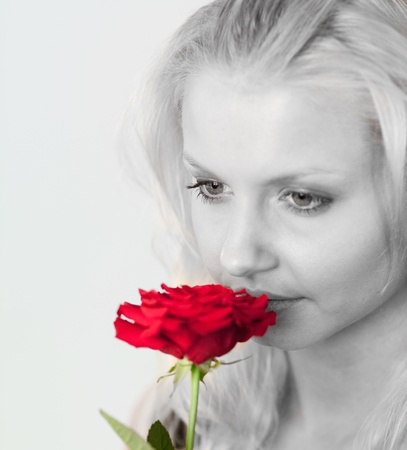 Radiant woman in black and white smelling a red rose  photo