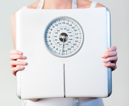 Close-up of a woman holding a scales with focus on scales  photo