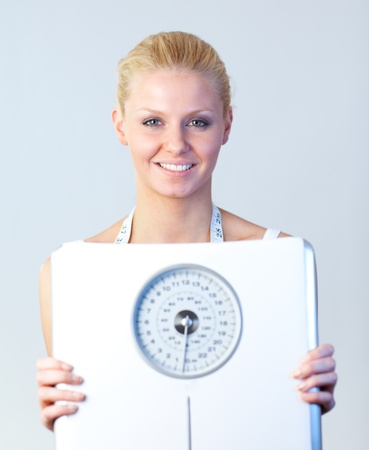 Friendly woman holding a scales focus on woman  photo