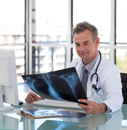 male doctor: Bella medico di sesso maschile l'esame di una radiografia Archivio Fotografico