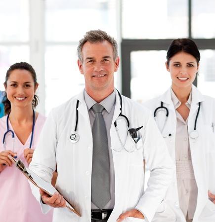 Senior Smiling läkare med sina kolleger