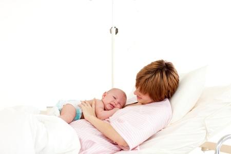 Patient speaking to her newborn baby in bed Stock Photo - 10110036