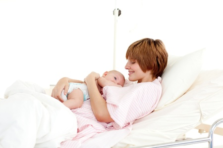 Smiling patient with newborn baby in bed Stock Photo - 10110789