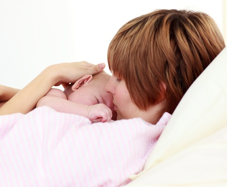 lookalike: Portrait of a patient kissing her newborn baby in bed
