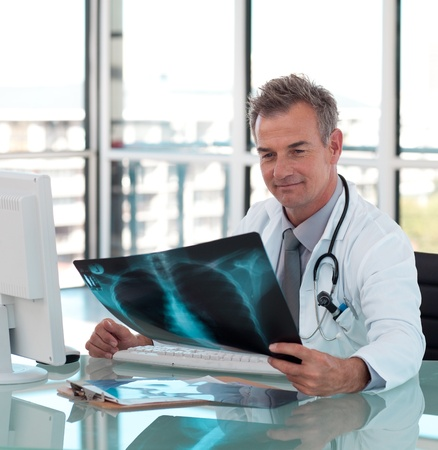 Mature male doctor examining a x-ray photo