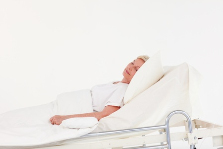 lying on bed: Senior patient lying on a medical bed Stock Photo