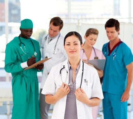 Vacker läkare med sitt team i bakgrunden
