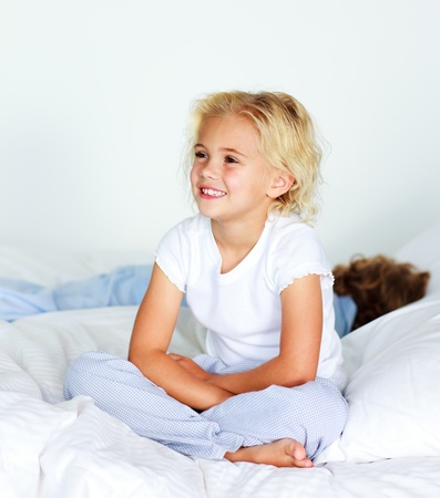 Little girl sitting on bed before sleeping photo