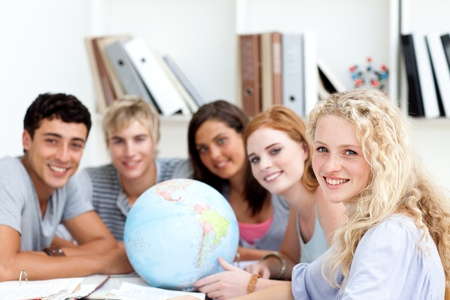 terrestrial: Smiling teenagers in a library working with a terrestrial globe