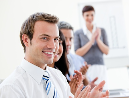 Smiling business people applausing a good presentation photo