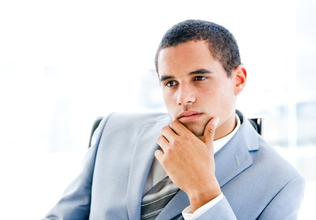 Portrait of a pensive young businessman sitting at his desk