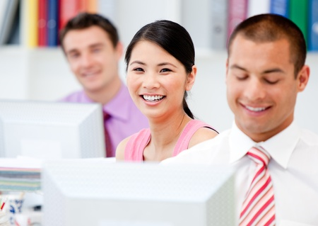 Happy business people working at a computer Stock Photo - 10111663