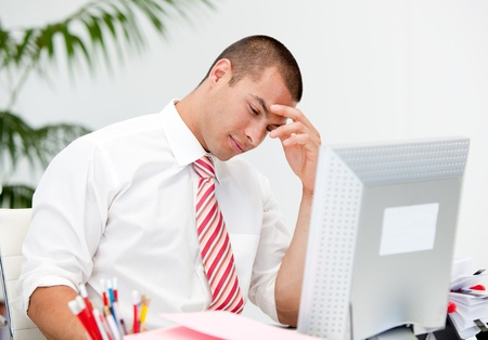afflict: Stressed businessman working at a computer  Stock Photo