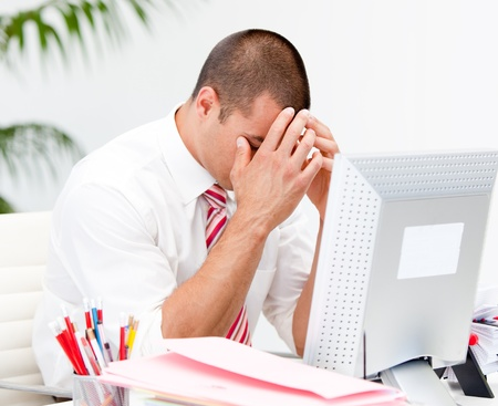 overwhelm: Frustrated businessman working at a computer